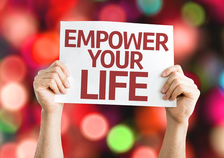empower: Hands holding Empower your Life card with bokeh background Stock Photo