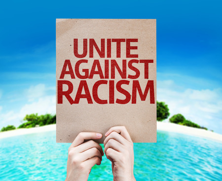 unite: Hands holding Unite Against Racism card with island background