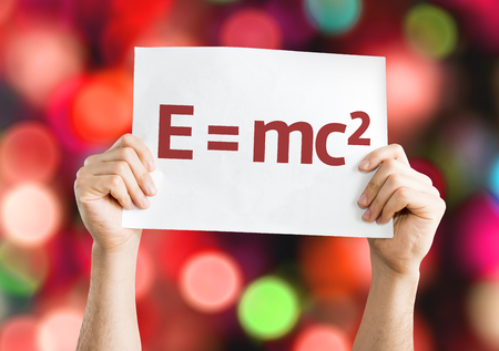 Hands holding E = mc2 card isolated on bokeh background Stock Photo