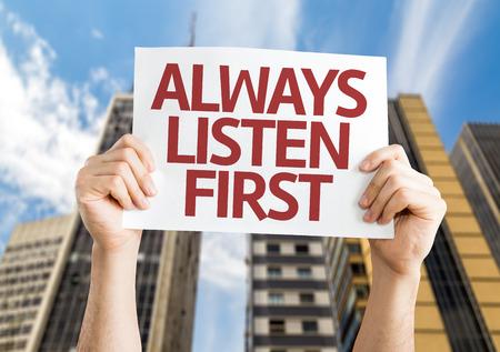 always listen first: Hands holding Always Listen First card with city background