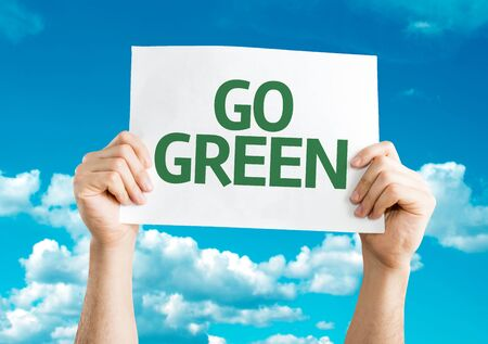 go green background: Hands holding card with text: Go Green with sky background