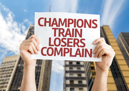 complain: Hands holding Champions Train Losers Complain card with city background