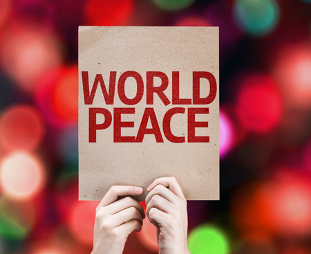 non violence: Hands holding World Peace card with bokeh background