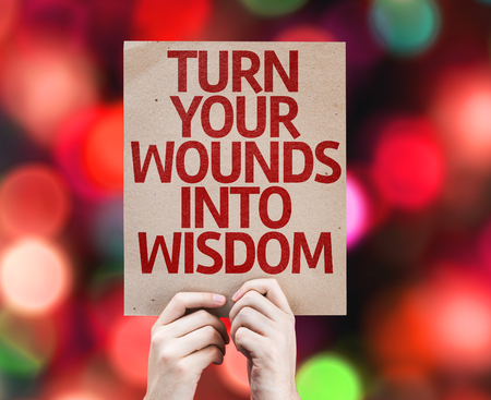 Hands holding Turn Your Wounds Into Wisdom card with bokeh background