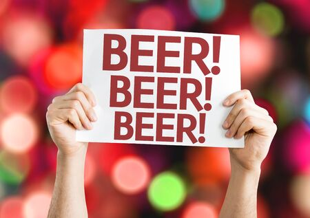 beverage display: Hands holding Beer card with bokeh background Stock Photo