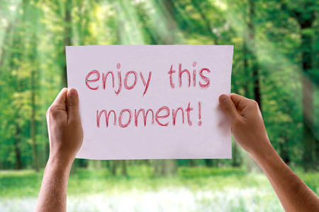 this: Hands holding Enjoy This Moment! card with nature background Stock Photo