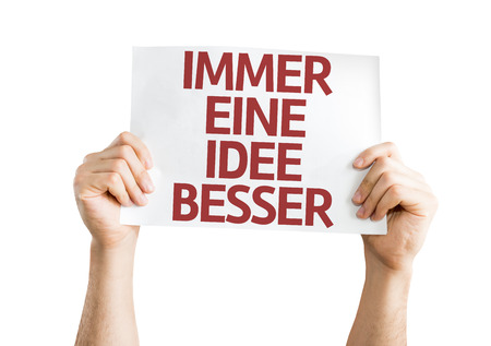 getting better: Hands holding Getting a Better Idea (in German) card isolated on white background