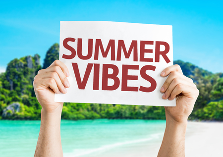 vibrations: Hands holding Summer Vibes card with beach in background Stock Photo