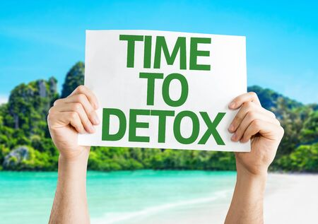 reducing: Hands holding Time To Detox card on beach background