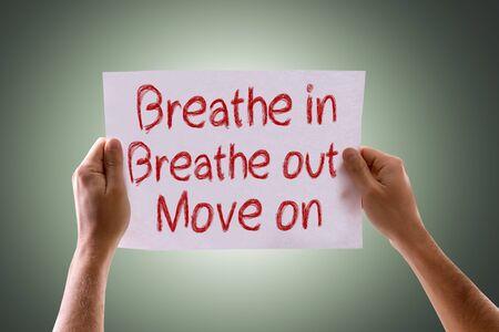 adentro y afuera: Manos que sostienen Breathe In Breathe salir Pasar tarjeta con fondo verde Foto de archivo