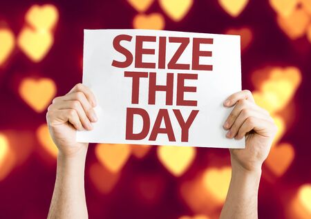 seize: Hands holding Seize The Day card on heart bokeh background