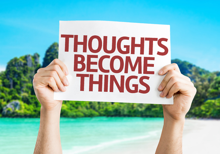 mental object: Hands holding Thoughts Become Things card on beach background Stock Photo