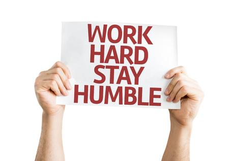 Manos que sostienen el trabajo duro estadía tarjeta de Humble aislados sobre fondo blanco