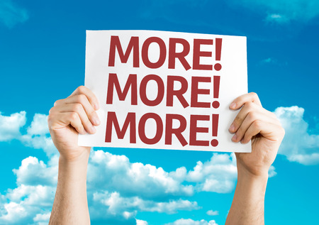 Hands holding More! More! More! card with sky background Standard-Bild