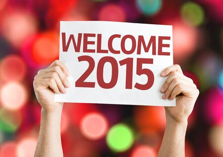 renewing: Hands holding Welcome 2015 card on bokeh background