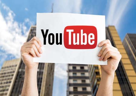 Hands holding YouTube card on city background Stock Photo