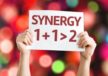 sinergia: Manos que sostienen la tarjeta de Sinergia 1 + 1> 2 con el fondo del bokeh
