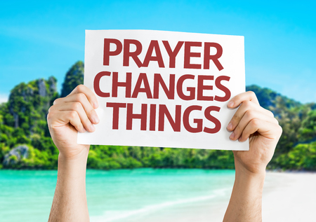 worshipper: Hands holding Prayer Changes Things card with beach background