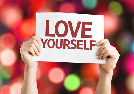 egoistic: Hands holding Love Yourself card with bokeh background Stock Photo
