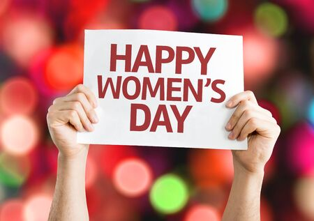 womens day: Hands holding Happy Womens Day card with bokeh background Stock Photo