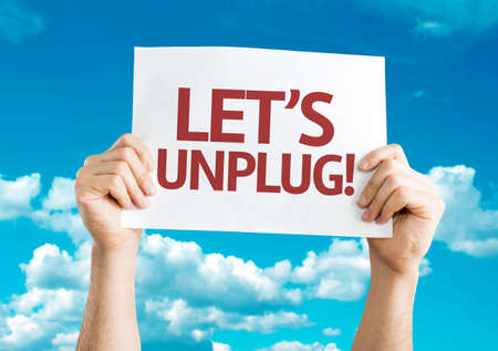 Hands holding Lets Unplug card with sky background