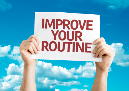 routine: Hands holding Improve Your Routine card with sky background