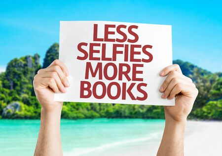 less: Hands holding Less Selfie More Books card with beach background