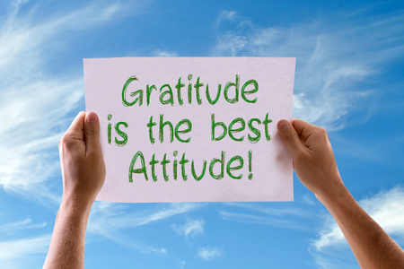 thankfulness: Hands holding Gratitude is the Best Attitude card with sky background Stock Photo