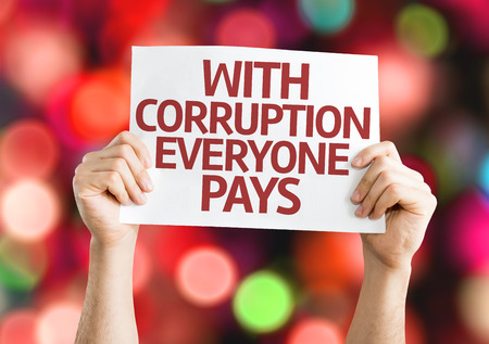 pays: Hands holding With Corruption Everyone Pays card with bokeh background Stock Photo