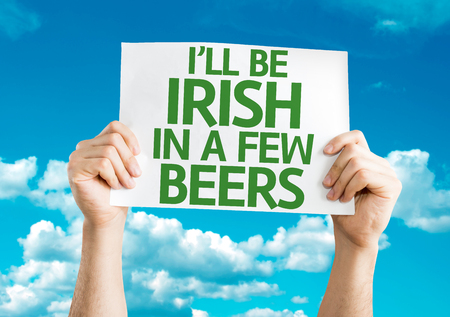 beers: Hands holding Ill Be Irish in a Few Beers card with sky background Stock Photo