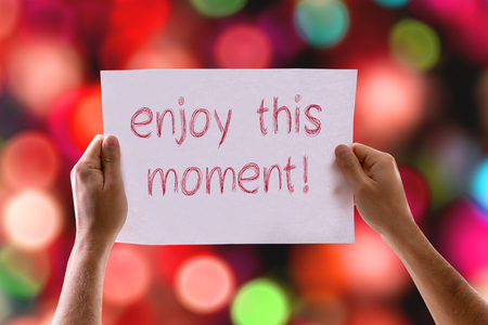 this: Hands holding Enjoy This Moment! card with bokeh background