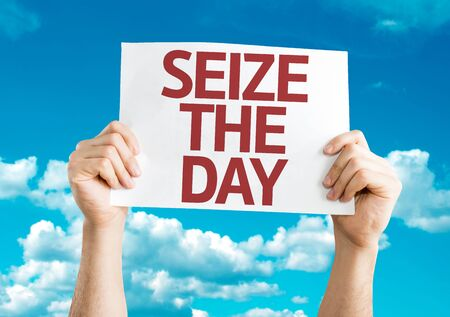 seize: Hands holding Seize The Day card on sky background Stock Photo