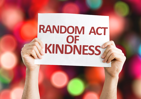 helpfulness: Hands holding Random Act Of Kindness card with bokeh background
