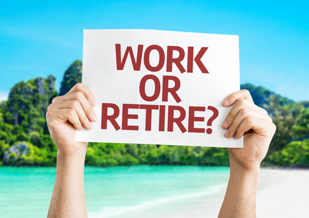 retire: Hands holding Work or Retire? card with beach background