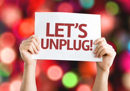 unplug: Hands holding Lets Unplug card with bokeh background Stock Photo