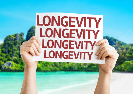 longevity: Hands holding Longevity card with beach background