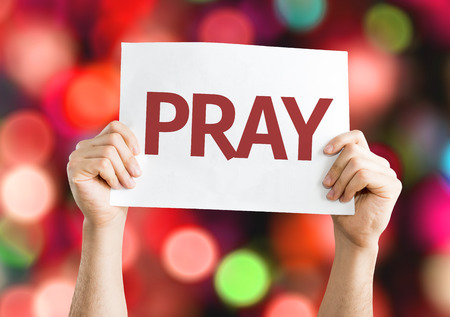 thankfulness: Hands holding Pray card with colorful background with defocused lights Stock Photo