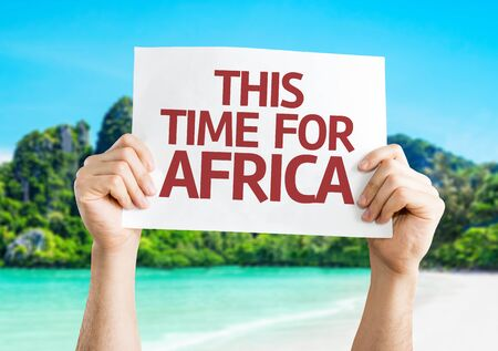 this: Hands holding This Time for Africa card with beach background