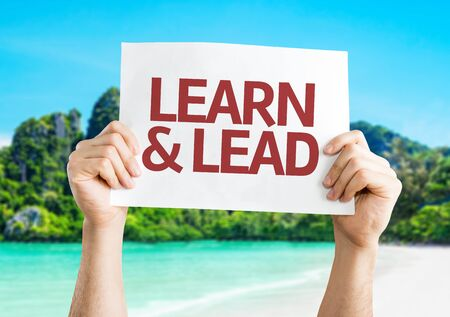 learn and lead: Hands holding Learn & Lead card with beach background Stock Photo