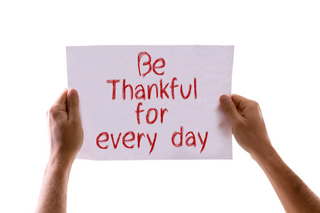 every: Hands holding Be Thankful for Every Day card isolated on white background
