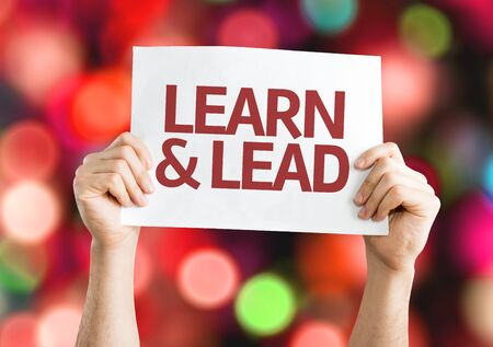 learn and lead: Hands holding Learn & Lead card with bokeh background