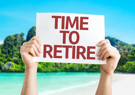 retire: Hands holding Time to Retire card with beach background Stock Photo