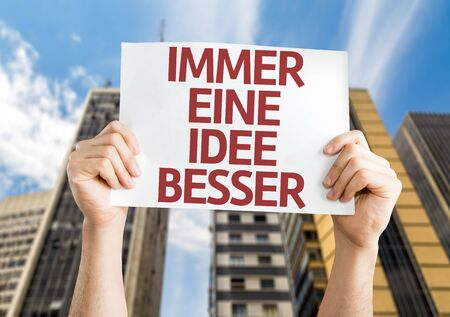 getting better: Hands holding Getting a Better Idea (in German) card with city background