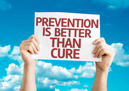 cure prevention: Hands holding Prevention is Better than Cure card with sky background Stock Photo