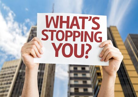 stopping: Hands holding Whats Stopping You? card with city background