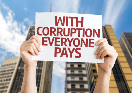 immoral: Hands holding With Corruption Everyone Pays card with city background Stock Photo