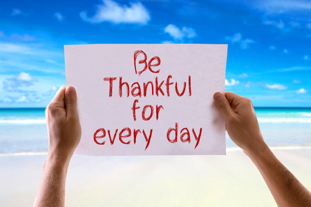 thankfulness: Hands holding Be Thankful for Every Day card with beach background
