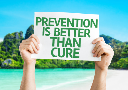 cure prevention: Hands holding Prevention is Better than Cure card with beach background Stock Photo