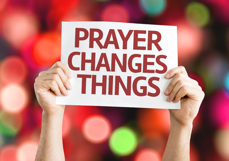 worshipper: Hands holding Prayer Changes Things card with bokeh background Stock Photo