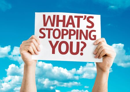 stopping: Hands holding Whats Stopping You? card with sky background